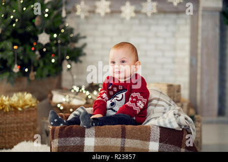 Pensive child boy is sitting against the background of the Christmas tree and festive garlands. - Stock Photo