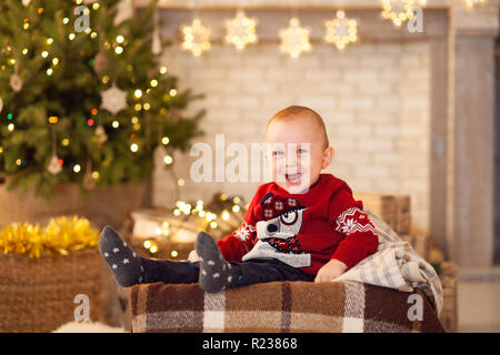 Cheerful child boy is sitting against the background of the Christmas tree and festive garlands. - Stock Photo