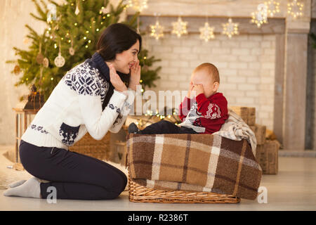 Mother comforts her little crying son on background of the Christmas tree and festive garlands. - Stock Photo