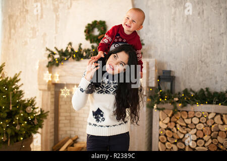Happy mother and her little son are playing on background of the Christmas tree and festive garlands. Mother carries her son on her shoulders and they - Stock Photo