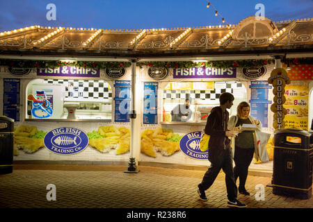 At a fish-and-chip stall on Brighton Pier a young man and woman are buying food. Overhead the roof has rows of light bulbs under an evening sky. - Stock Photo