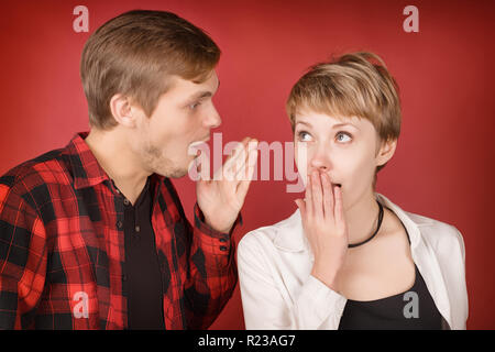 Young man talking something to surprised woman. On red studio background - Stock Photo