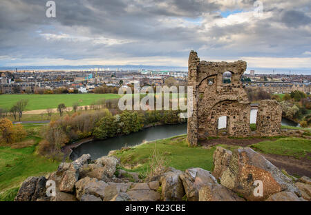 The romantic ruin folly of St Anthony's Chapel stands on the hillside of Arthur's Seat above St Margaret's Loch in Holyrood Park in Edinburgh. - Stock Photo