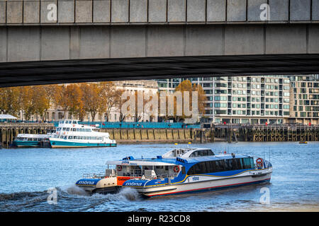 LONDON - NOVEMBER 13 : A city cruises tour sails on the Thames River sightseeing boat goes under the bridge on 13 November 2018 in London, England UK - Stock Photo