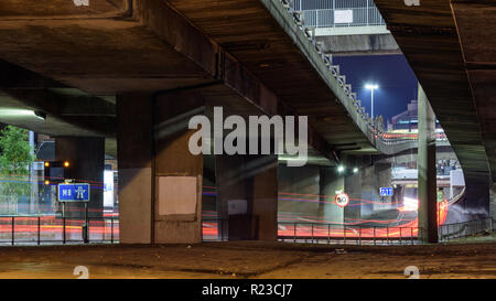 Glasgow, Scotland, UK - November 6, 2018: Traffic leaves light trails amongst a tangle of concrete flyovers and slipway roads at the M8 motorway Ander - Stock Photo