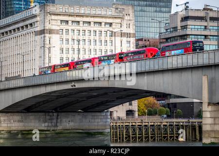 NOVEMBER 13, 2018, London, United Kingdom : Iconic new red London double decker passenger buses over the Thames in London Bridge. - Stock Photo