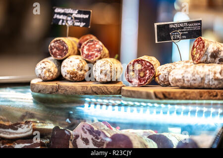 Various types of Dried organic salami sausage and saucisson on wooden cutting board in a store market - Stock Photo