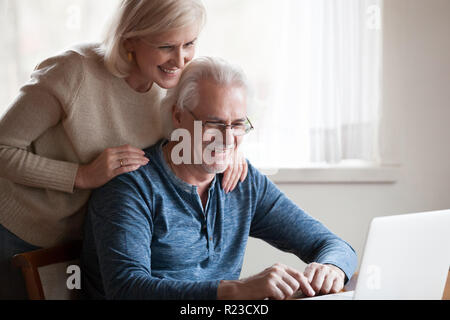 Excited aged husband using laptop showing smiling wife something on screen, happy senior couple looking at computer, watching pictures together or fun - Stock Photo