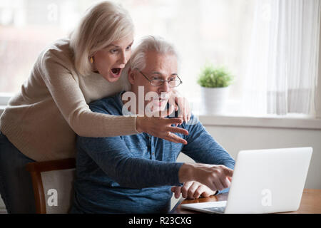 Shocked senior husband and wife pointing at laptop screen seeing unbelievable information, surprised aged couple notice unexpected on computer, elderl - Stock Photo