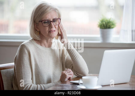 Upset aged woman using laptop at home suffering from headache, tired senior female massaging temples having severe pain or blurry vision, exhausted el - Stock Photo