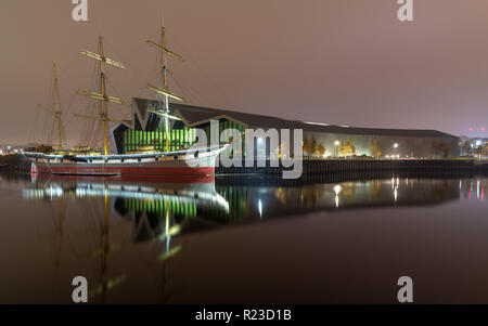Glasgow, Scotland, UK - November 5, 2018: The Clyde-built tall ship Glenlee is lit at night outside the Riverside Museum of Transport in the Partick n - Stock Photo