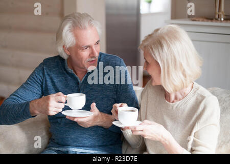 Happy senior couple enjoy tea sitting on cozy couch looking at each other talking, smiling aged husband and wife drink hot coffee having conversation  - Stock Photo