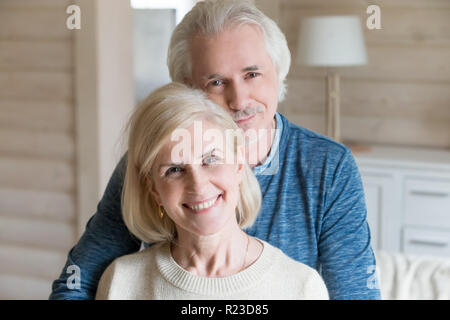 Portrait of happy aged couple hugging posing for family picture at home, caring senior husband embrace wife from behind shooting together, loving elde - Stock Photo