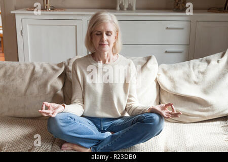 Calm senior woman relax on couch meditating in lotus position, peaceful aged female practice yoga at home relieve stress or renew energy, elderly lady - Stock Photo