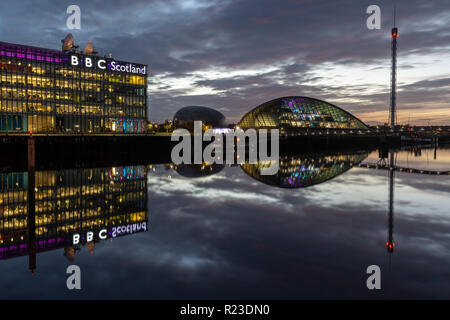 Glasgow, Scotland, UK - November 4, 2018: The modern offices and studios of BBC Scotland, and the Scottish Science Centre and Tower, are lit at night  - Stock Photo