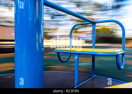 the carousel seat rotates with a blurred background - Stock Photo
