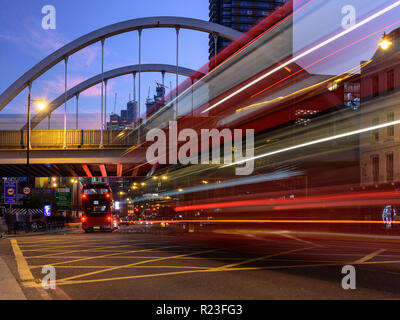 London, England, UK - October 20, 2018: Red double-decker buses leave light trails as they move along Shoreditch High Street, under London Overground' - Stock Photo