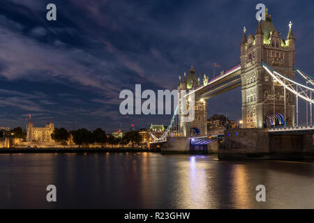 London, England, UK - September 27, 2018: Traffic crosses the River Thames on the iconic Tower Bridge, lit up at dusk, with the Tower of London beyond - Stock Photo