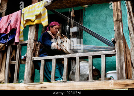 India, Himachal Pradesh, Old Manali, 08/12/2010: a woman works on a loom on the balcony of her home in the village of Old Manali - Stock Photo