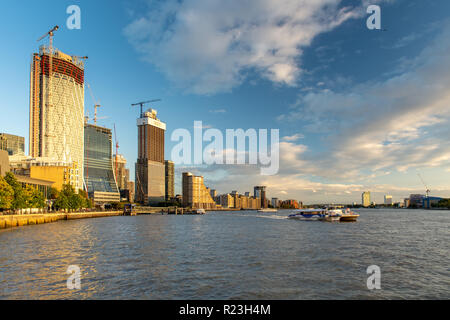 London, England, UK - September 14, 2018: A Thames Clipper ferry leaves Canary Wharf pier under a cluster of new skyscrapers currently being built on  - Stock Photo