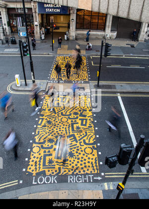 London, England, UK - September 10, 2018: Pedestrians cross a main road on a pelican crossing painted with jaunty patterns ourside Barbican tube stati - Stock Photo