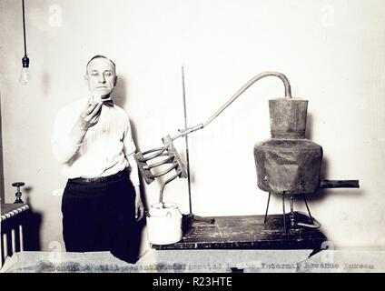 Moonshine still recently confiscated by the Internal Revenue Bureau photographed at the Treasury Department. Man standing next to still looking at contents of glass. 1921 - Stock Photo