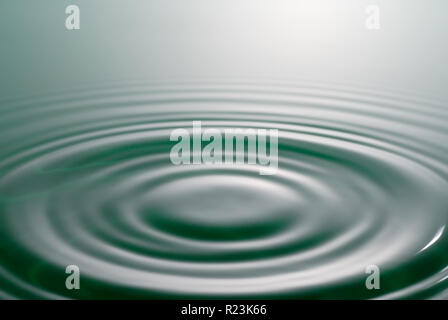 Tranquil scene. Symmetrical circles and waves on water surface. - Stock Photo