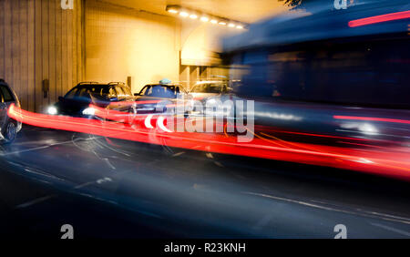 Night traffic on city streets. Cars queued at tunnel exit waiting at intersection while driving vehicles moving past leaving color light trails - Stock Photo