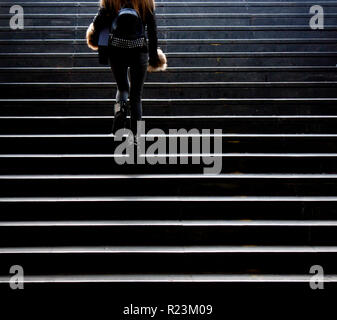 Blurry young woman in grunge outfit climbing up the city street public stairs, from behind - Stock Photo