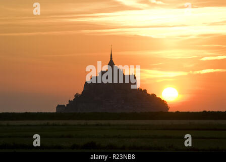 Sun sets behind Mont-Saint-Michel (Le Mont-Saint-Michel), an island commune in Normandy, France known for its monastery and fortifications. - Stock Photo