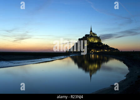 Sun sets behind Mont-Saint-Michel (Le Mont-Saint-Michel), an island commune in Normandy, France known for its monastery and fortifications. Stock Photo