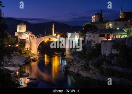 Night time view of the city of Mostar lit up along the river, featuring the rebuilt arched bridge: 'Stari Most'. - Stock Photo