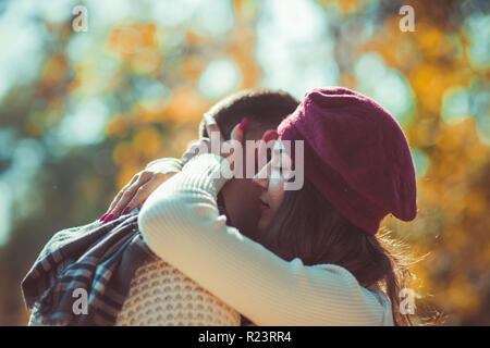 Sweet couple is outdoors in nature, looking peacefully and hugging - Stock Photo