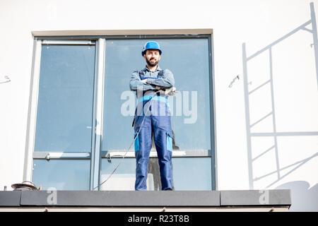 Portraiit of a builder in uniform standing on the balcony of a new house on the construction site - Stock Photo
