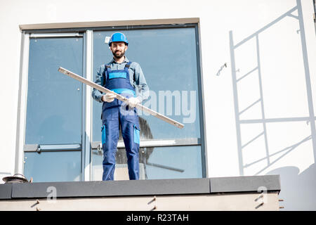 Portraiit of a builder in uniform standing with level on the balcony of a new house on the construction site - Stock Photo