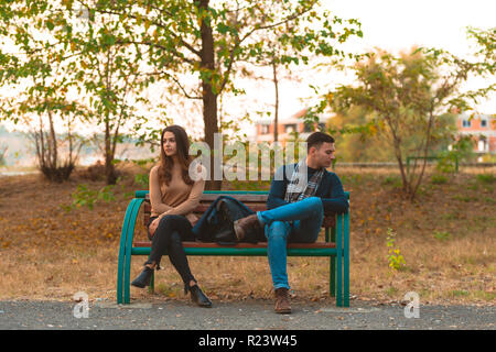 Angry couple sitting on a bench and looking in opposite directions. - Stock Photo