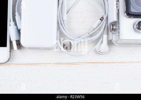 White technology on natural wooden table background. Power bank, cable, headphones, action camera, smartphone. Copy space at the bottom. Flat lay top  - Stock Photo