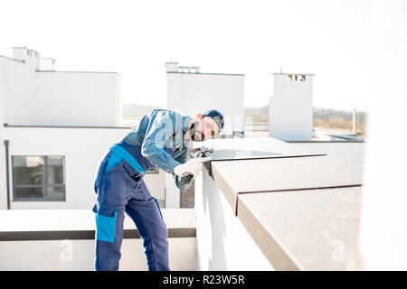 Builder in uniform mounting metal cover on the parapet of a new building - Stock Photo