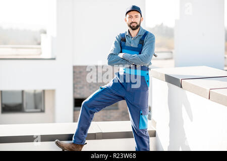 Portrait of a builder in uniform on the roof of a new white building outdoors - Stock Photo
