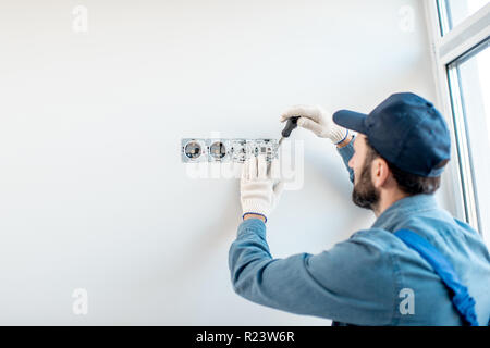 Electrician in uniform mounting electric sockets on the white wall indoors - Stock Photo