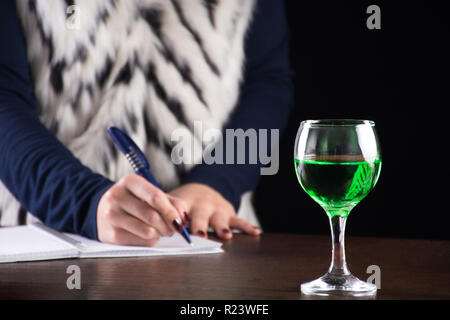Absinthe green drink in glass and woman writing story notebook in background on old retro wooden desk. Green fairy inspiration and muse for writer - Stock Photo