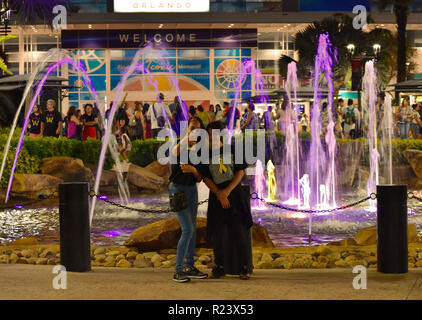 Orlando, Florida. October 18, 2018. Friends taking selfie on magenta iluminated water fountain in International Drive area. - Stock Photo