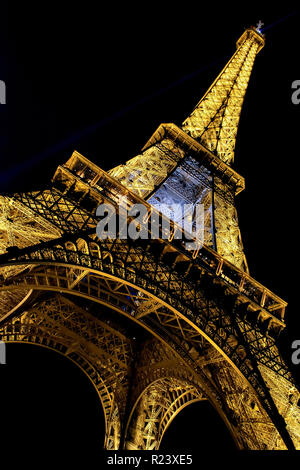 PARIS - MAY 27, 2015: Eiffel Tower brightly illuminated at dusk in Paris. The Eiffel tower is the most visited monument of France. - Stock Photo