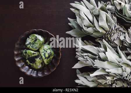 Bowl of Nephrite Jade Stones with White Sage Smudges on Brown Table - Stock Photo