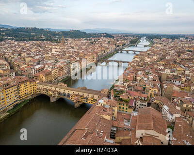 Aerial view of the Ponte Vecchio over the Arno river in Firenze Florence with cloudy sky on a summer morning in Tuscany Italy - Stock Photo