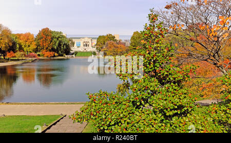 The Wade Park Lagoon in Cleveland, Ohio, USA encircled by fall colored trees showcases the Cleveland Museum of Art in the distance. - Stock Photo