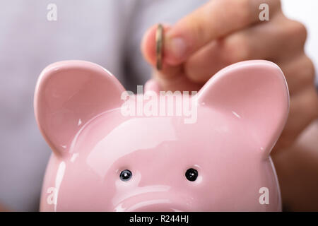 Close-up Of A Person's Hand Inserting Coin In Pink Piggybank - Stock Photo