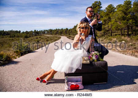 Newlywed couple pose on their sofa in the middle of a lonely road with vintage phones - Stock Photo