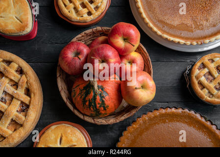 Above view of kitchen table with a wicker basket with apples and pumpkins in the middle, and various traditional pies, pumpkin pies, and apple pies. - Stock Photo