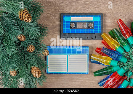 Retro blue audio cassette and christmas decorations on bown wooden background - Stock Photo